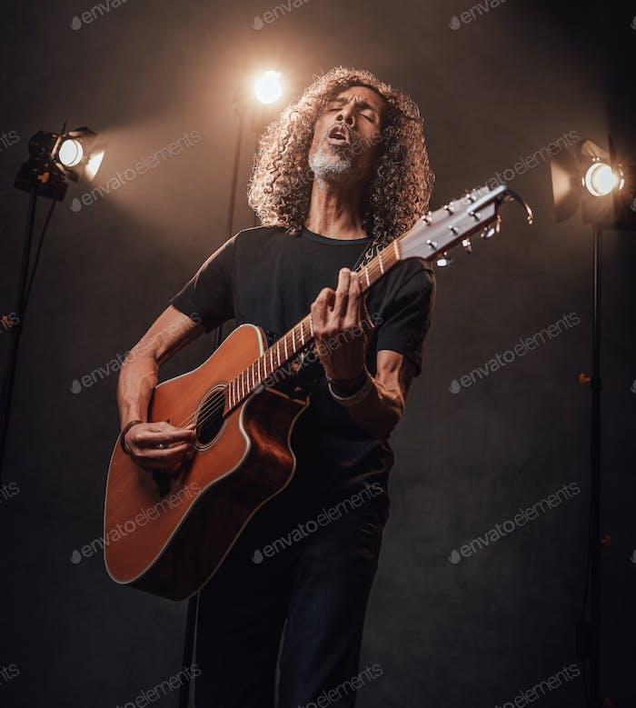 Mittelalter hispanischer Musiker in schwarzem T-Shirt emotional singen und Gitarre spielen
