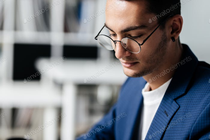 Portrait of dark-haired young architect in glasses dressed in blue checkered jacket