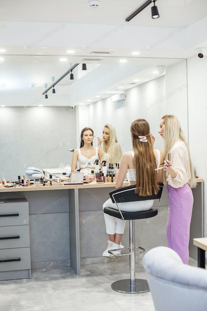 Makeup artist makes makeup to a girl. Apply beige eye shadow. Close-up. Vertical
