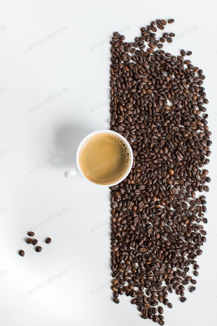 top view of cup of coffee and scattered coffee beans isolated on white