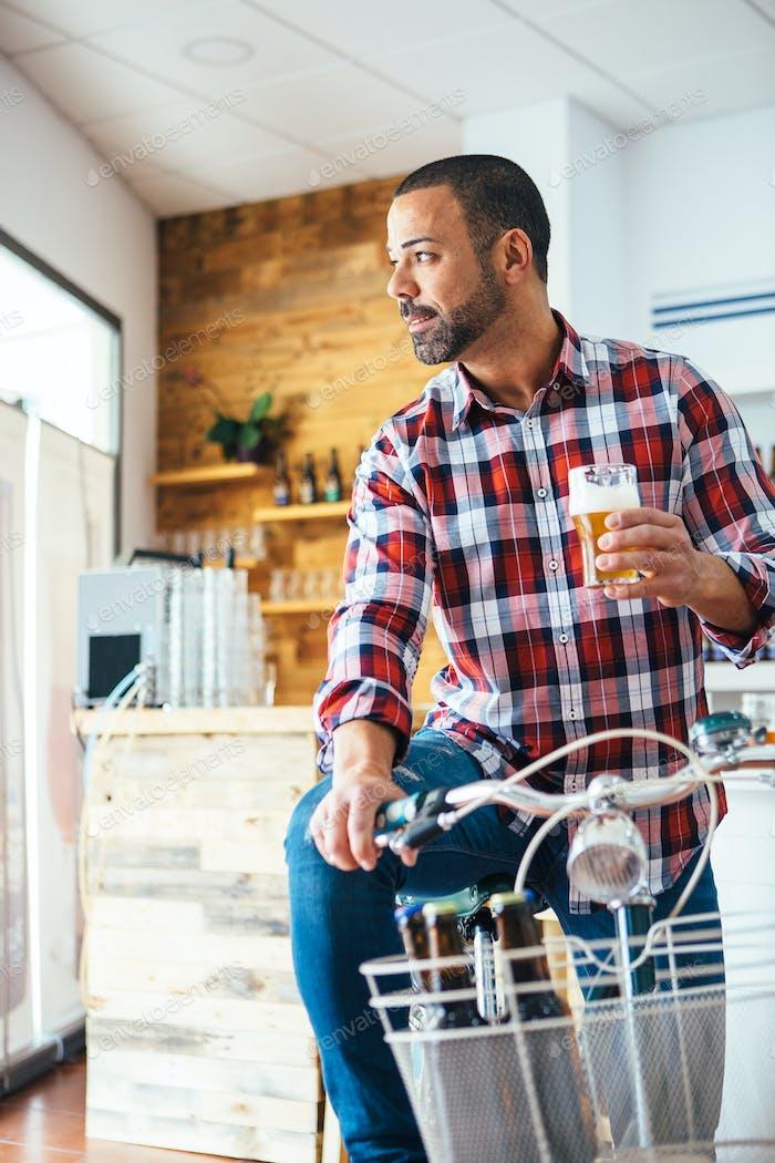 Man with beer on bike indoor