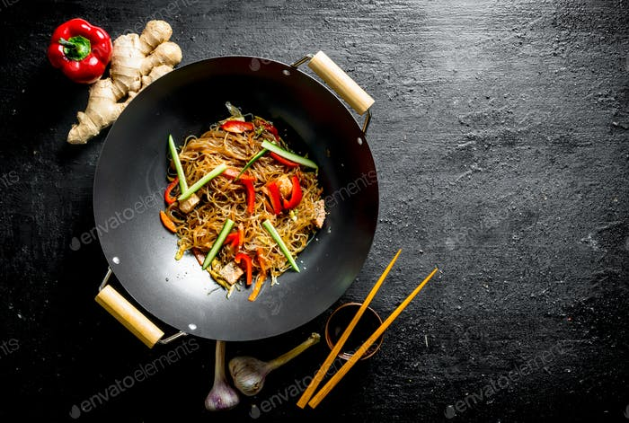 Delicious cellophane noodles in a frying pan wok with chopsticks.