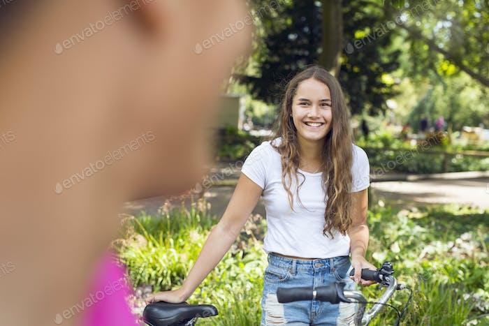 Teenage boy and teenage girl (14-15) in park