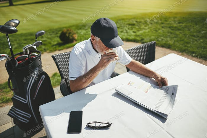 Senior man sitting with coffee at his golf club restaurant