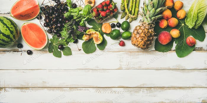 Flat-lay of seasonal fruit, vegetables and greens over wooden background