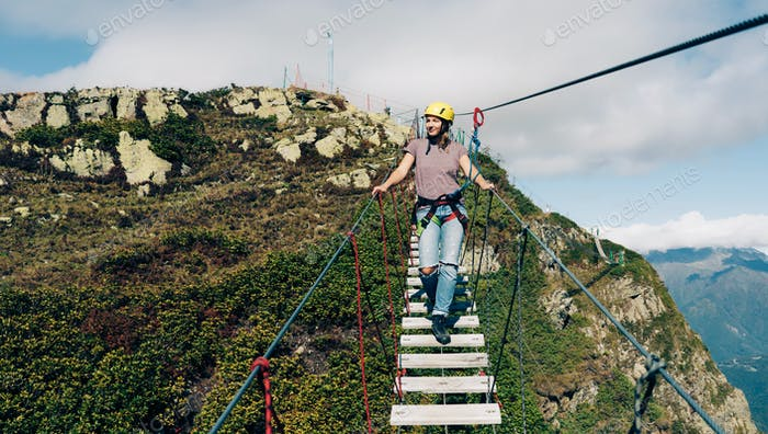 woman in safety equipment and helmet on a rope suspension bridge high in the mountains