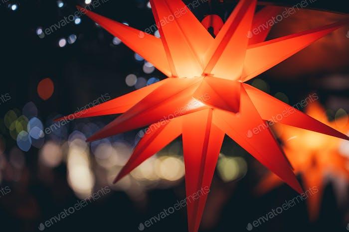 Red colored stars illuminated with light on Xmas tree at Christmas Market in Hamburg, Germany