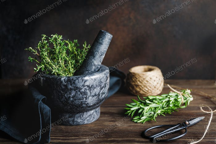 Fresh herbs in a marble mortar on a table