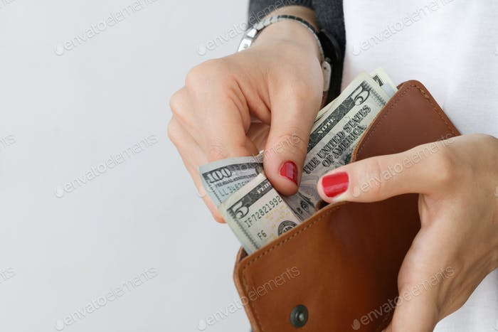 The girl holding an open leather orange slim wallet with cash dollars against white wall.