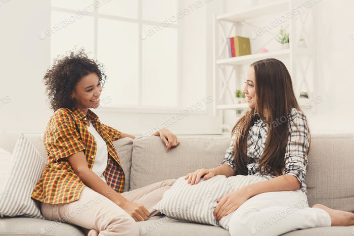 Two young female friends conversing at home