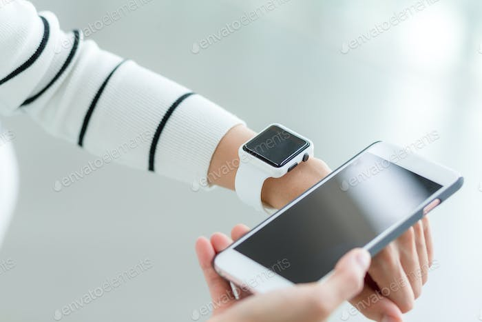 Woman connecting smartwatch and mobile phone