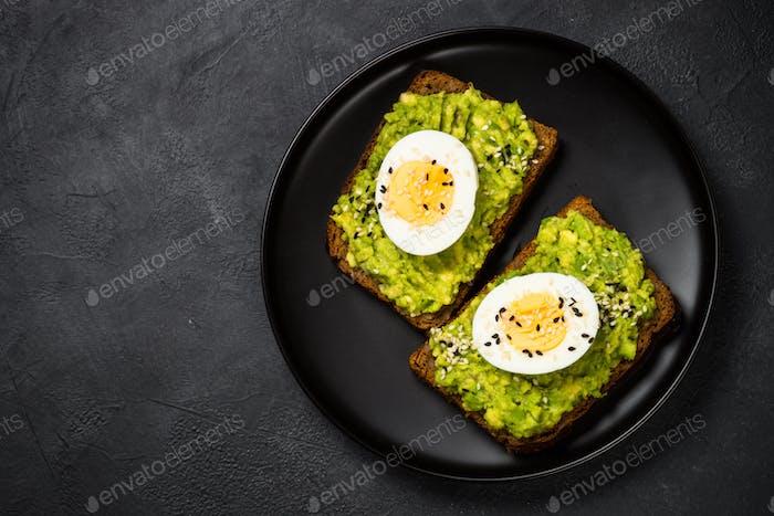 Avocado Sandwiches auf schwarzem Hintergrund