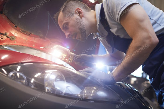 Professional Mechanic Inspecting Car in Auto Shop