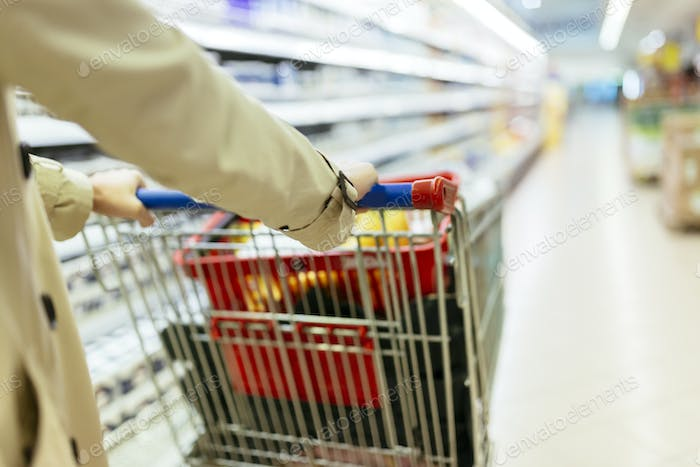 Woman pushing shopping trolley