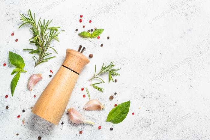 Pepper mill with fresh herbs on white