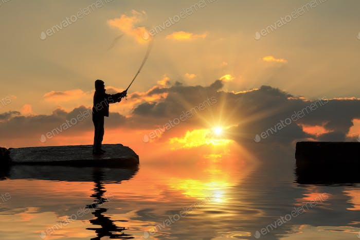 Fisherman on pier at sunset