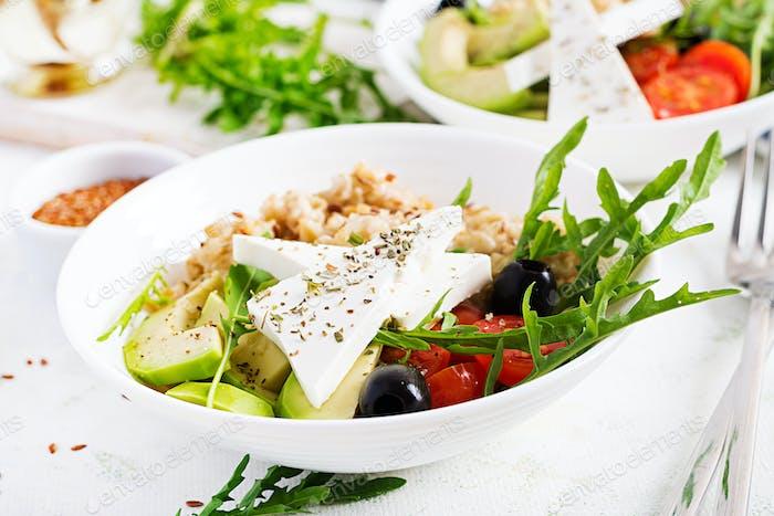 Breakfast oatmeal porridge with greek salad of tomatoes, avocado, black olives