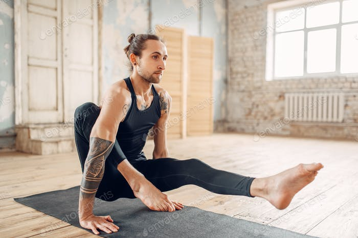 Male yoga relax in gym, balance exercise on mat