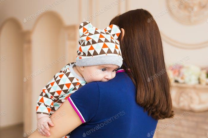 Entzückendes kaukasisches Baby mit seiner Mutter. Porträt eines drei Monate alten Jungen, Rückansicht