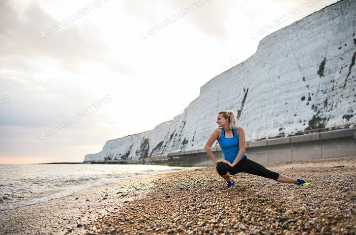 Young sporty woman runner in blue sportswear stretching on the beach outside.