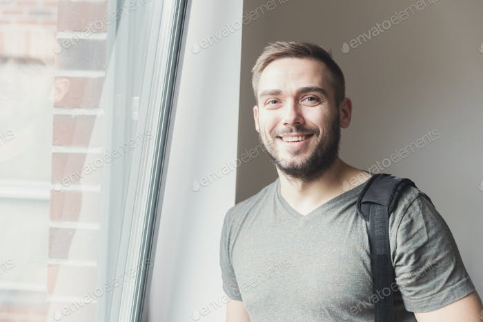 Young man smiling next to the window.