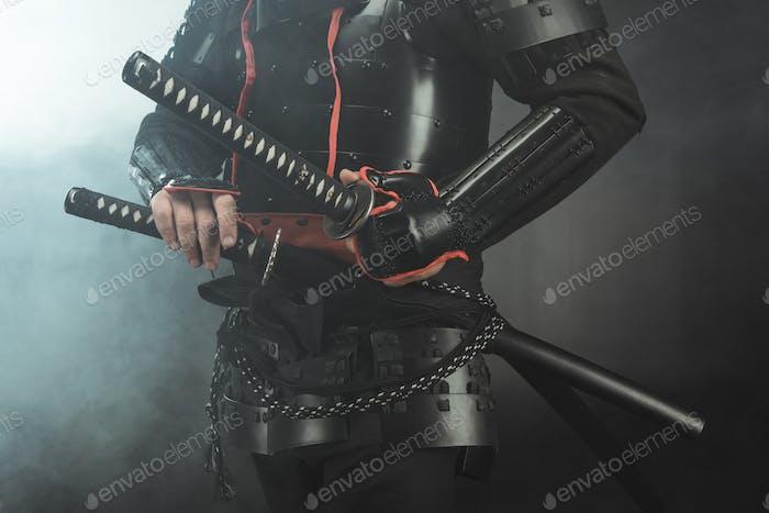 beschnittene Aufnahme von Samurai in Rüstung mit Schwertern auf dunklem Hintergrund mit Rauch
