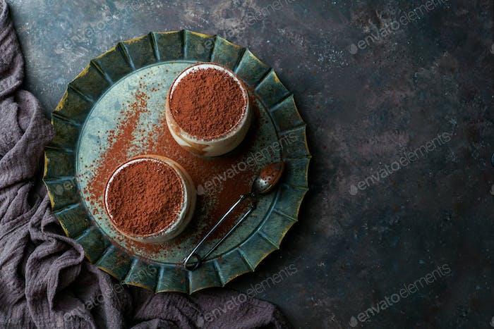 tiramisu dessert in glasses on dark concrete background
