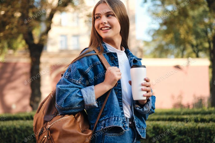 Cheerful student girl in denim jacket with coffee happily looking away in college campus