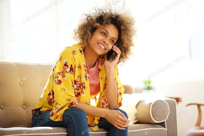 schöne afrikanische amerikanische Mädchen sitzen auf couch reden auf handy