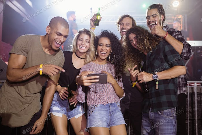 Cheerful friends looking at mobile phone in nightclub