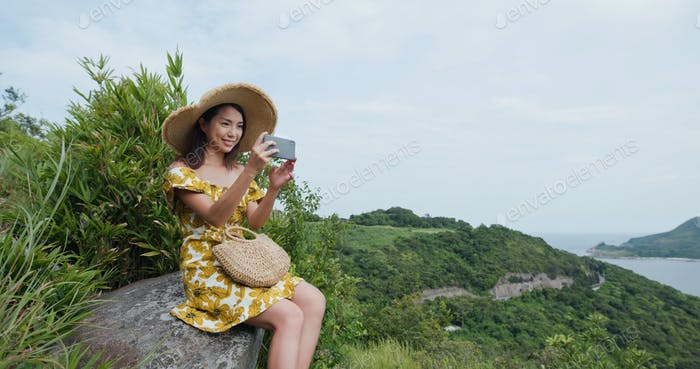 Woman go hiking and take photo on cellphone on mountain