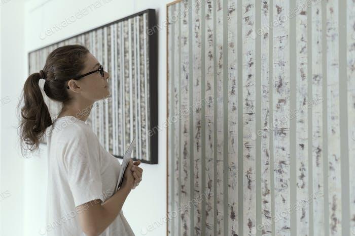 Frau steht in der Kunstgalerie und Blick auf die Gemälde