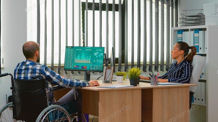 Geschäftsmann im Rollstuhl arbeitet im Geschäftsbüro
