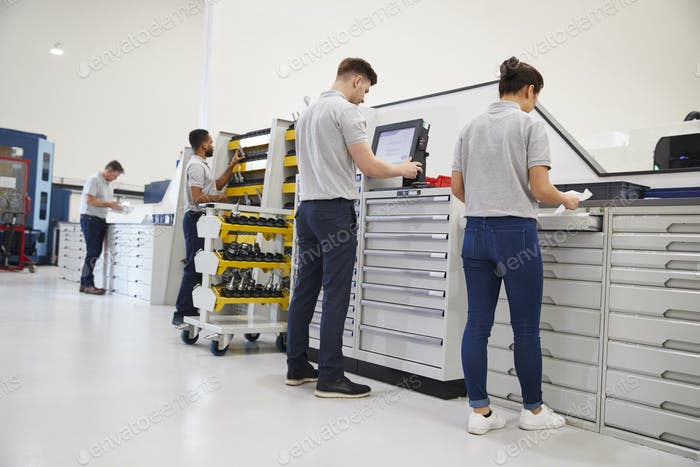Engineers Selecting Tools For Use On Machinery In Factory
