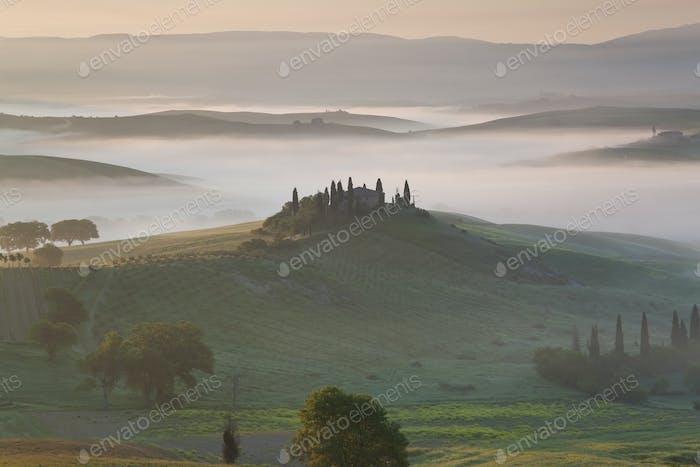 Sunrise across a misty Italian landscape of rolling hills