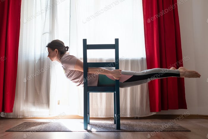 Young woman practicing yoga in Superman Pose or Viparita Shalabhasana using chair