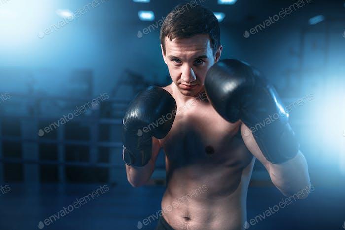 Портрет мускулистого боксера в черных перчатках