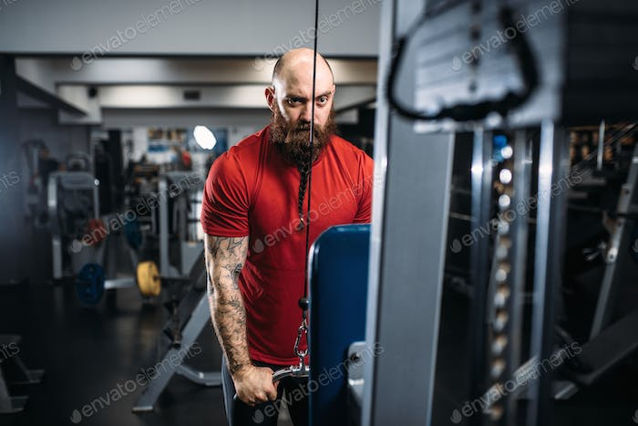 Athletic male person, training on exercise machine