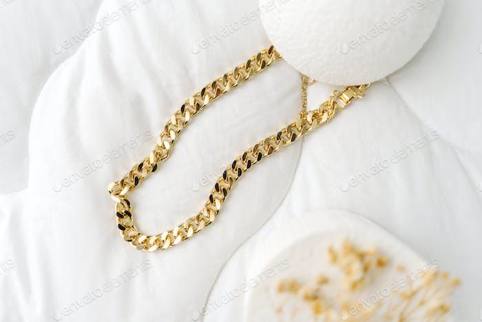 Goldene moderne Bijouterie-Kette auf weißem Hintergrund.