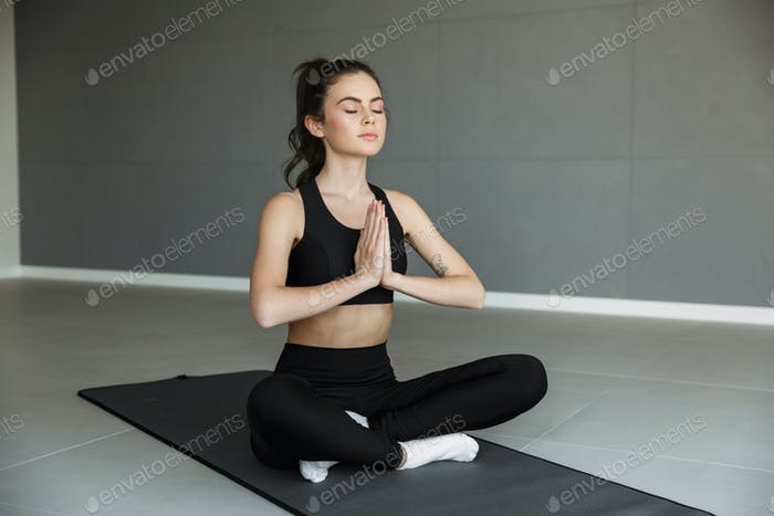 Photo of focused young woman meditating and holding palms together