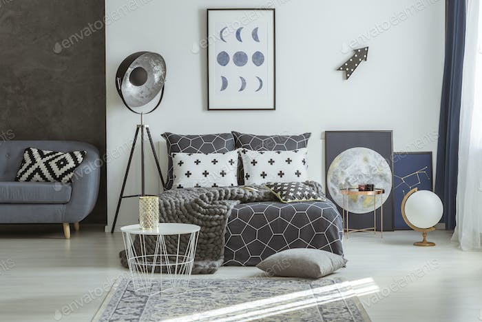 Astronomical posters in grey bedroom interior