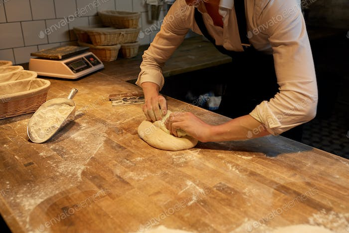 chef or baker cooking dough at bakery