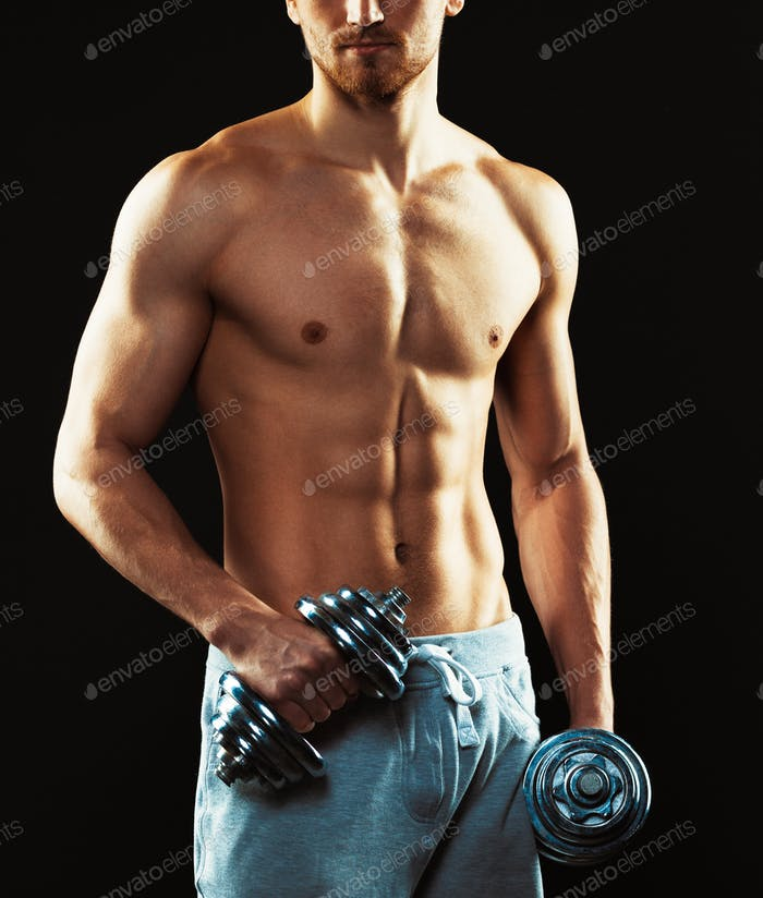 Athletic man with dumbbells on the black