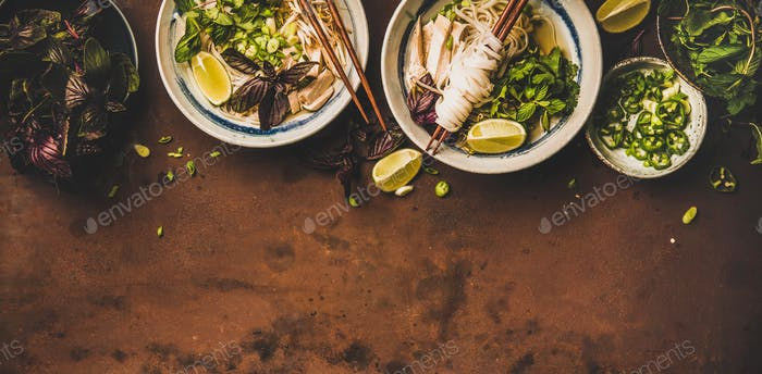 Flat-lay of Vietnamese lunch with soup Pho Ga, wide composition