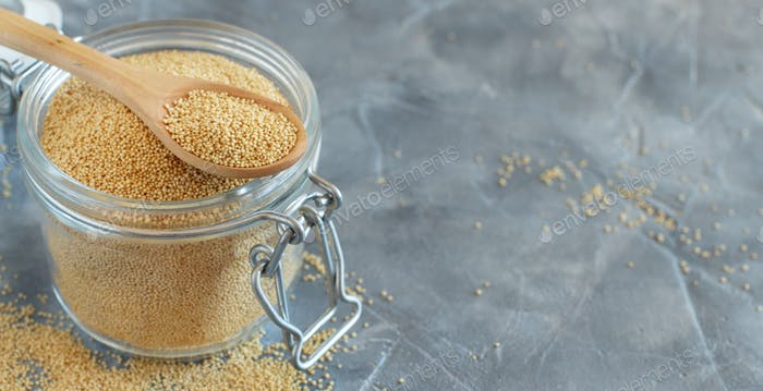 Jar of raw Amaranth seeds with a spoon