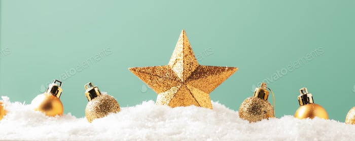 Christmas background with golden star. New Year's decor. Christmas balls in snowdrifts