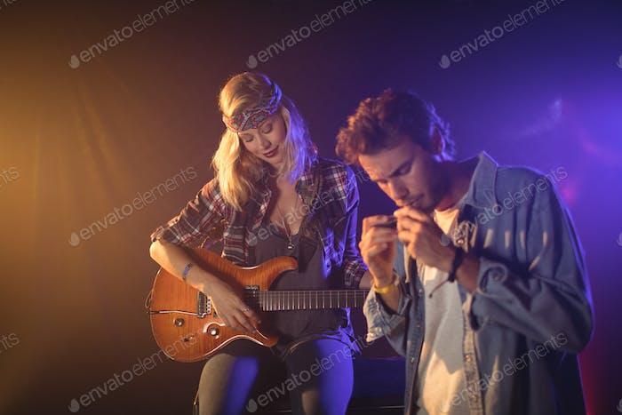 Gitarrist mit Musiker spielen Mundharmonika im Nachtclub