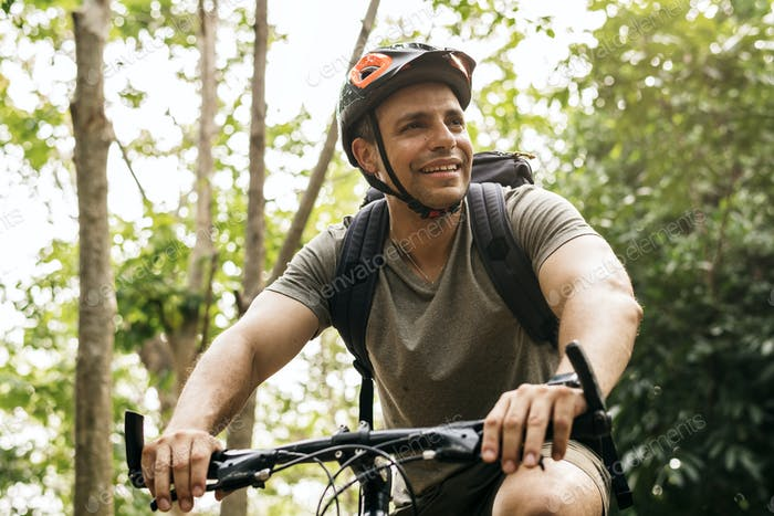 Happy cyclist riding through the forest