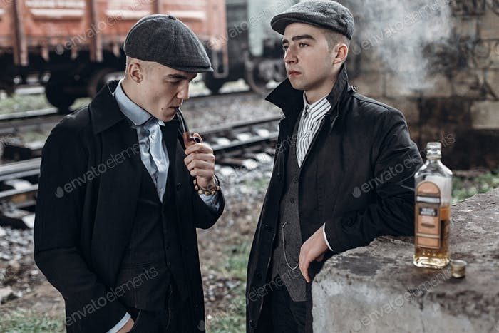 Stylish gangsters men, smoking posing on background of railway with bottle of alcohol