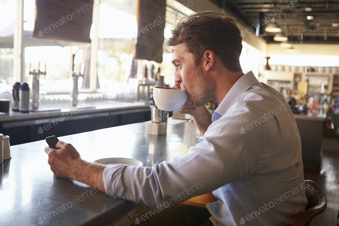 Man Checking Messages On Phone In Coffee Shop